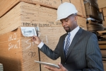 African American male contractor using tablet PC while inspecting wooden planks